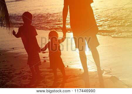 silhouette of father and two kids walking at sunset