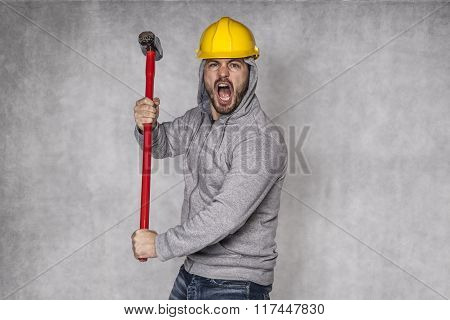 Builder On A Grey Background, Holding A Hammer And Shouting