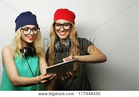 two hipster girls friends use digital tablet