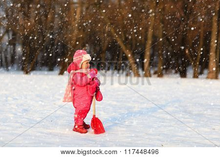cute little toddler girl dig in winter snow