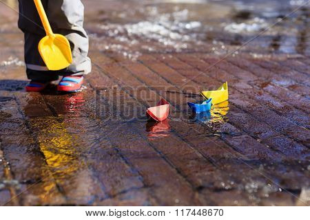 child playing with paper boats in spring puddle