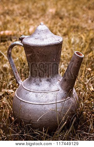 Old Metal Pitcher On Yellow Grass