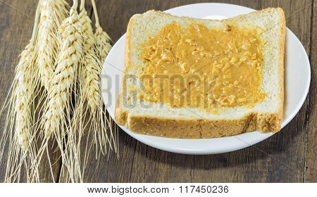 Selective Focus Of Bread And Peanut Butter On Wood Background With Wheat