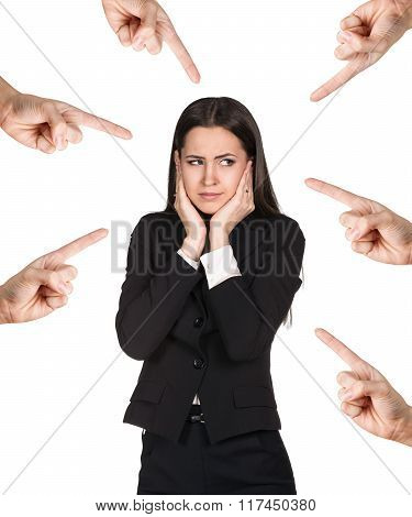 Many hands points on business woman