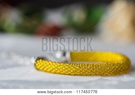 Crochet Beaded Bracelet From Beads Of Yellow Color On Textile Background
