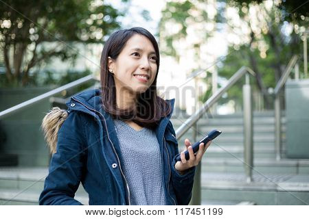 Woman look far away with cellphone