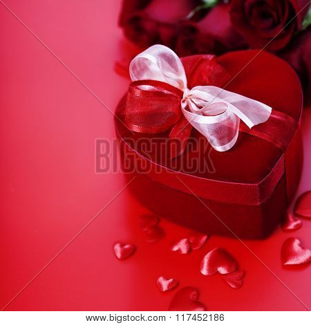 Valentine composition with roses and gift box on red background
