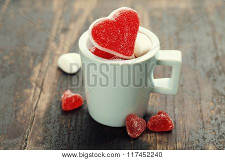 Valentine composition with hearts in a blue cup on wooden background