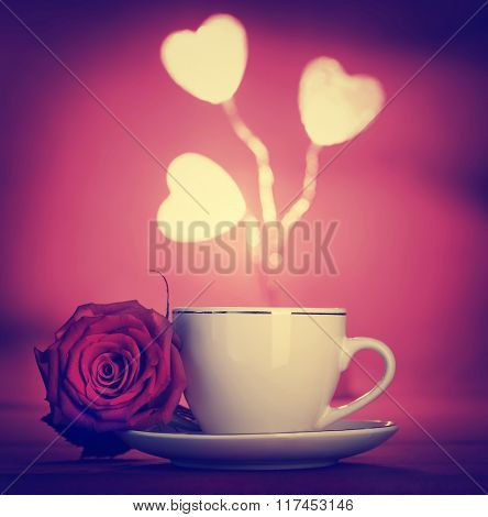 Vintage style photo of a coffee cup with red rose flower and white hearts decoration over red background, Valentine's day celebration