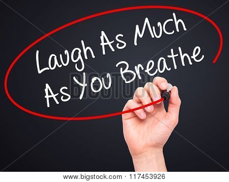 Man Hand Writing Laugh As Much As You Breathe With Black Marker On Visual Screen.