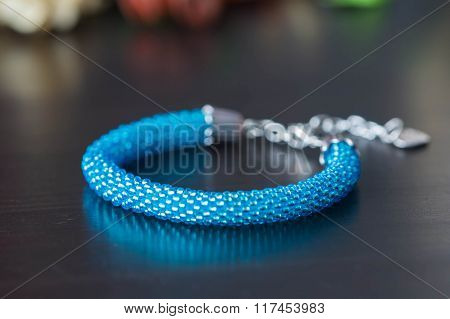 Shiny Handmade Bracelet From Beads Of Turquoise Color On A Dark Background