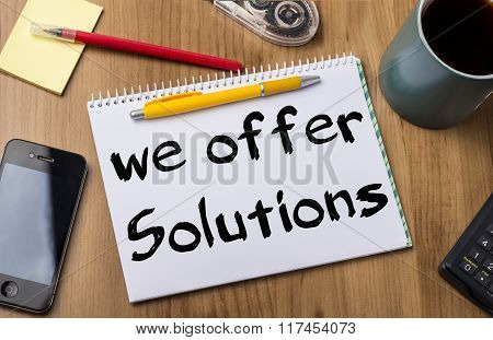 We Offer Solutions - Note Pad With Text On Wooden Table