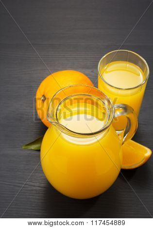 glass pitcher and orange juice on wooden background