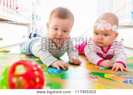Baby boy and girl twins playing with the ball at home