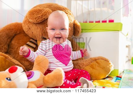 Baby girl portrait with huge teddy bear