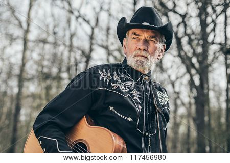 Senior Bearded Male Guitarist Standing At Forest