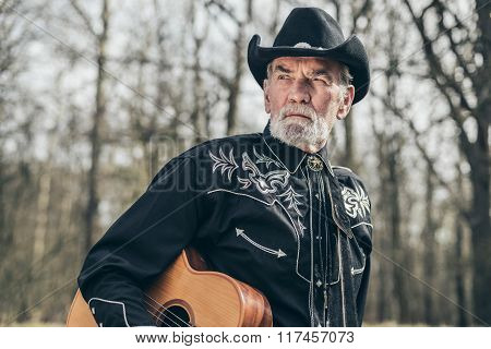 Pensive Bearded Old Man With Guitar At The Forest