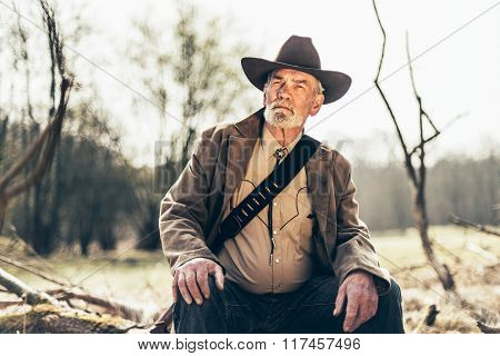 Pensive Senior Western Man Sitting At The Woods