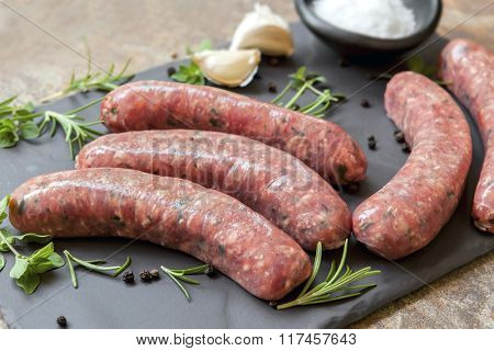 Raw sausages on slate, with herbs and spices. Side view.
