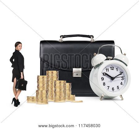 Business woman near alarm,briefcase and coins