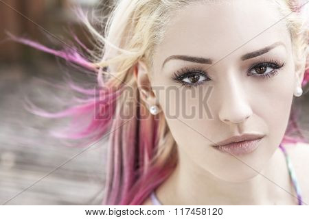 Outdoor portrait of a beautiful young woman or girl with brown eyes, blond and magenta pink hair