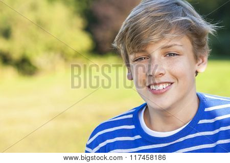Young happy smiling male boy teenager blond child outside in summer sunshine wearing a blue sweatshirt