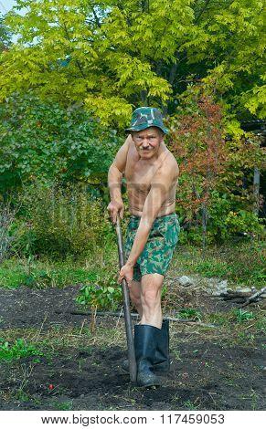 Man Digs With Spade