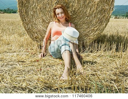 Young Farmer Woman Is Sitting And Leaning At The Haystack During Harvest By Summer, Rural Scene