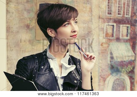 Young fashion business woman with a pen