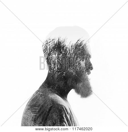 Double exposure portrait of a savage bearded man and a trees