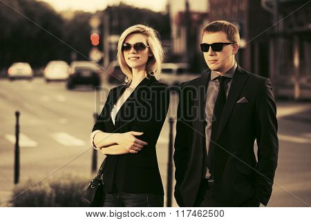 Young fashion business couple walking on city street