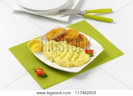 plate of mashed potato puree with chopped chives and breaded turkey breast on green place mat