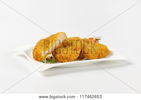 plate of breaded turkey breasts on white background