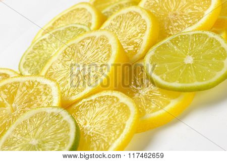heap of fresh lemon and lime slices on white background