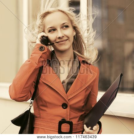Young fashion business woman with a folder calling on cell phone
