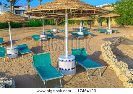 Sun umbrellas and empty deckchairs on the shore sand beach