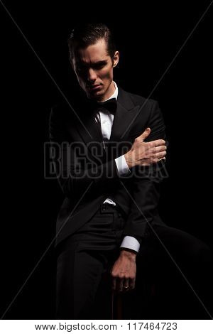 handsome businessman pose seated in dark studio background while looking at the camera and touching his arm