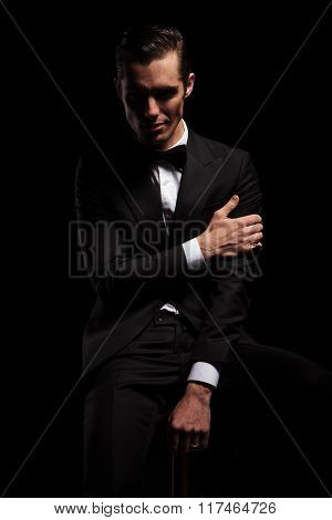 elegant attractive man in black suit with bowtie pose seated touching his arm while looking at the camera in dark studio background