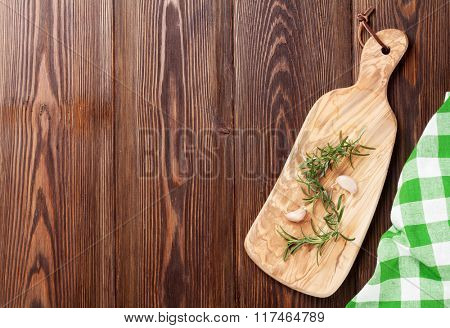 Rosemary and garlic on wooden table. Top view with copy space