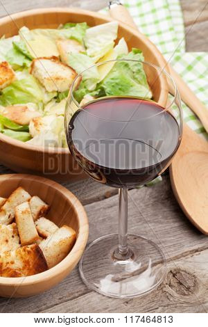 Fresh healthy caesar salad and red wine on wooden table