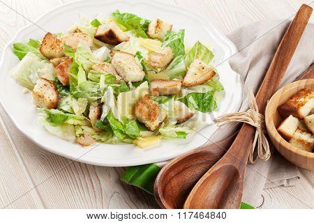 Fresh healthy caesar salad on wooden table