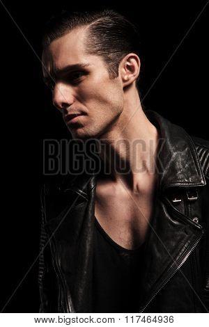 close portrait of confident biker in black leather jacket posing in dark studio background looking away