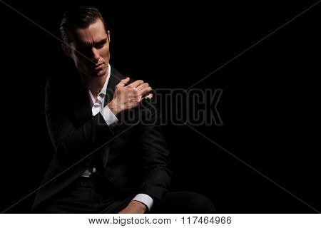 attractive man in black suit looking away while posing with hand on shoulder in dark studio background