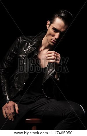 attractive man in black leather jacket posing seated in dark studio background while resting hands and looking at the camera