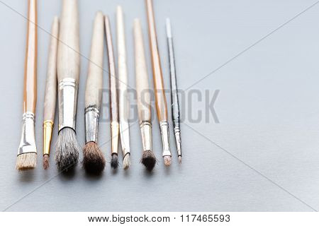 Used, vintage paintbrushes on gray background. macro view different size wooden and textured paint b
