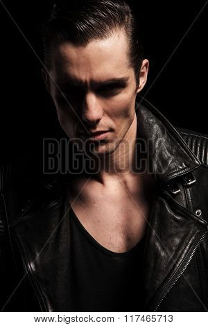 close portrait of sexy rocker in black leather jacket posing in dark studio backgound looking at the camera