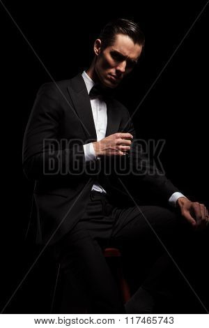side portrait of businessman in black posing seated in dark studio background while looking down and resting his arms
