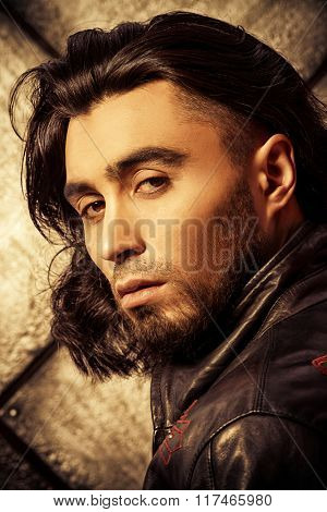 Stylish man in leather jacket over grunge background. Fashion shot.
