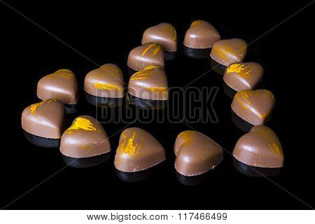 Milk chocolates heart from side on black