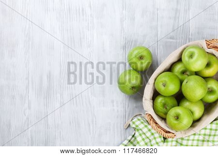 Green apples in basket over wooden table. Top view with copy space